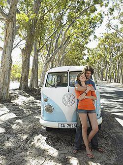 Zagreljeni par stoji pored starog VW kombija