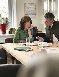Muškarac i žena sjede za radnim stolom i rade, na stolu papiri, šalice, čaše i zeleni GRAWE rokovnik