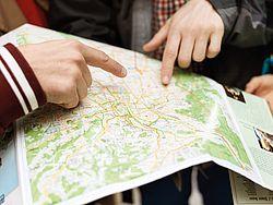 Zemljopisna karta, dvije ruke na njoj, kažiprstima pokazuju na neko mjesto na karti
