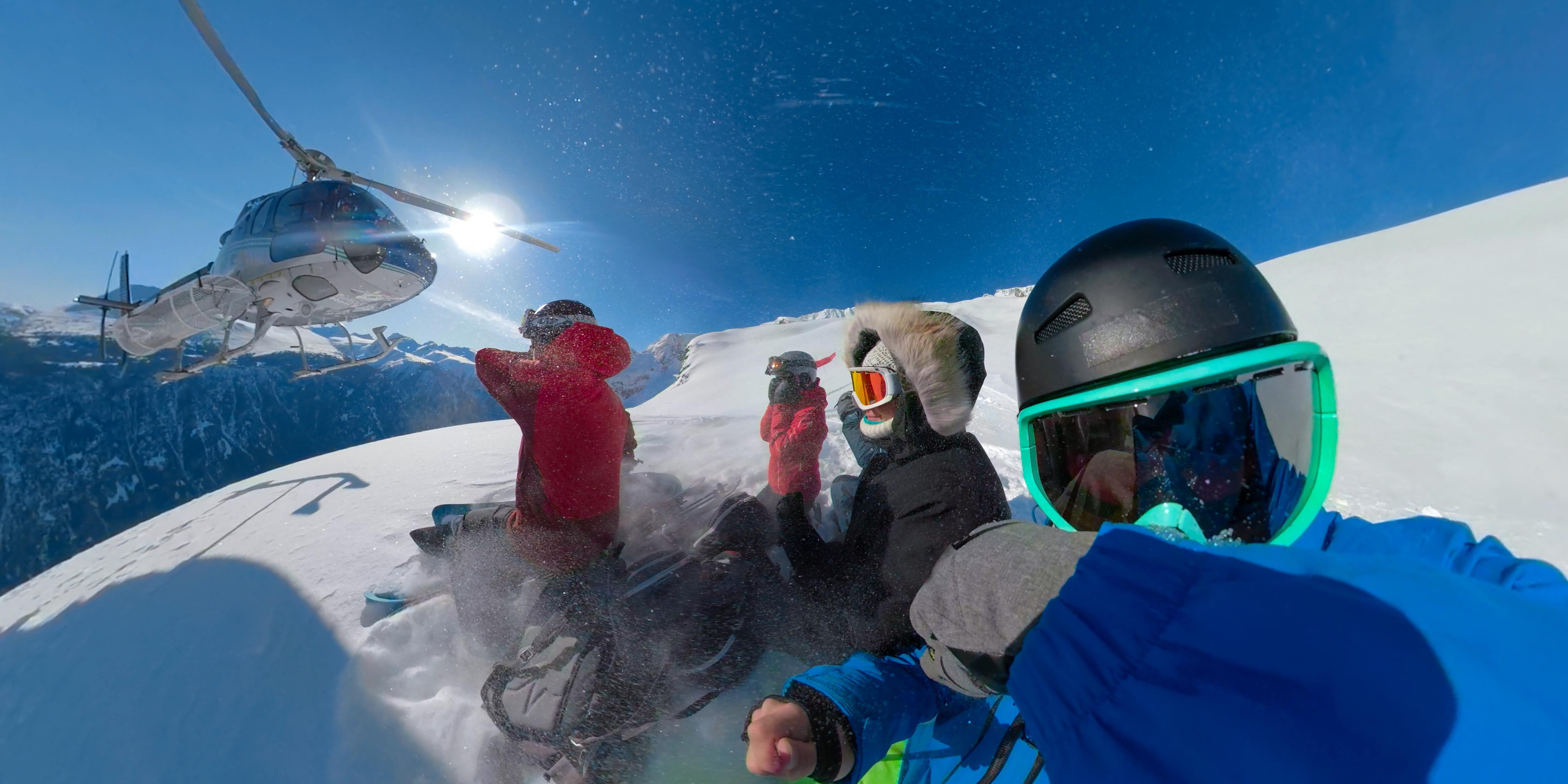 Skijaši/bordaši na vrhu snježne planine gledaju dolazak helikoptera