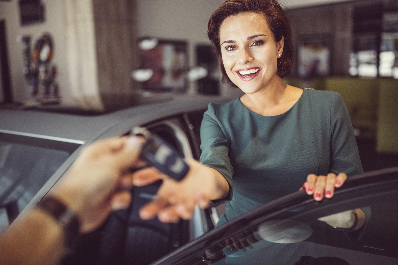 Djevojka pruža ruku prema drugoj ruci kako bi uzela automobilski ključ