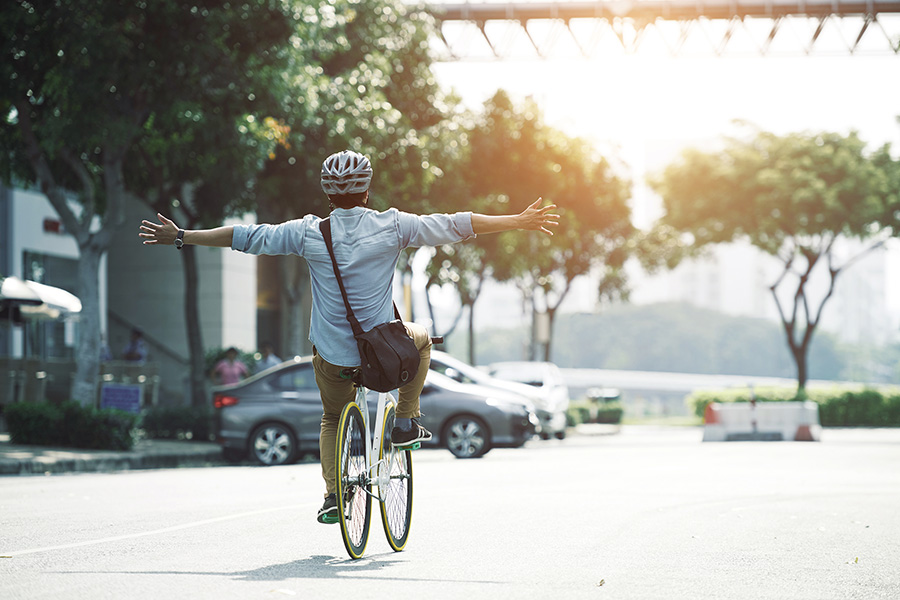 A men driving a bike with arms outstretched