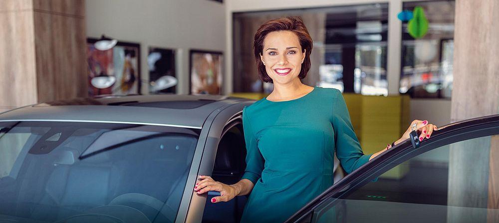 Žena stoji pored automobila otvorenih vrata vozača