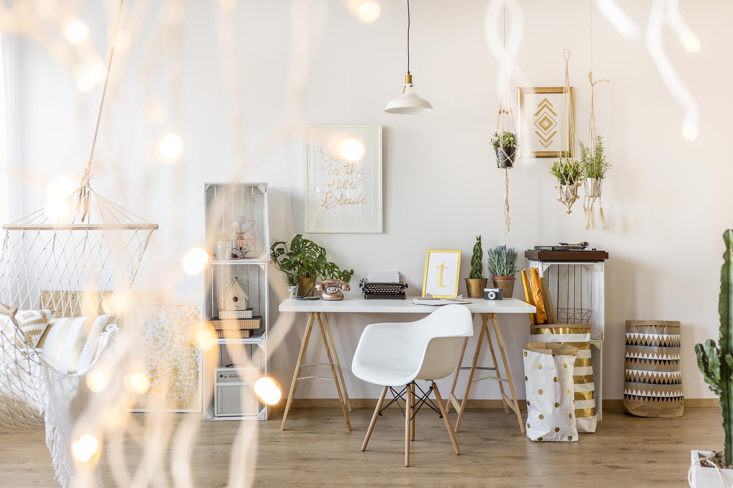 Dnevna soba s bijelim namještajem, radni stol i stolac, ljuljačka za ležanje usred sobe