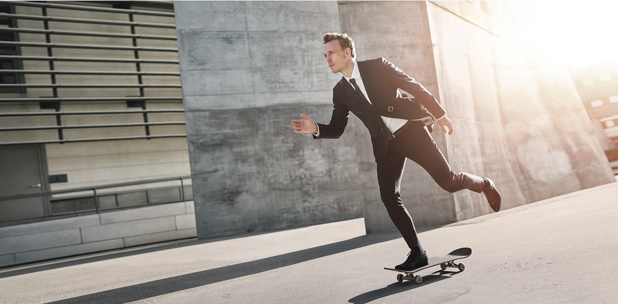 Muškarac u odijelu se vozi na skateboardu