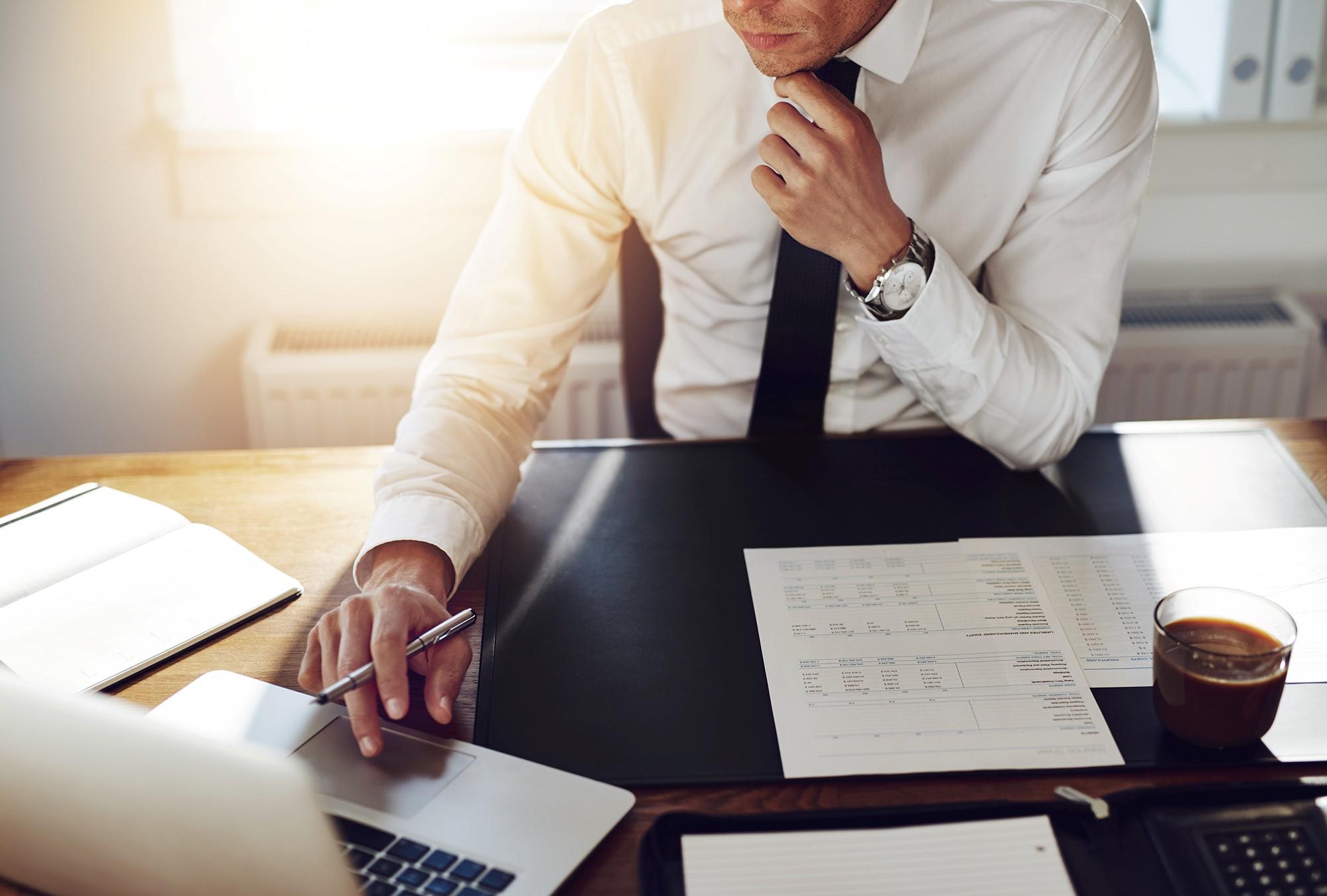 Muškarac za radnim stolom, vidi se ruka s kemijskom olovkom na prijenosnom računalu, na stolu rokovnik, papiri i šalica s kavom