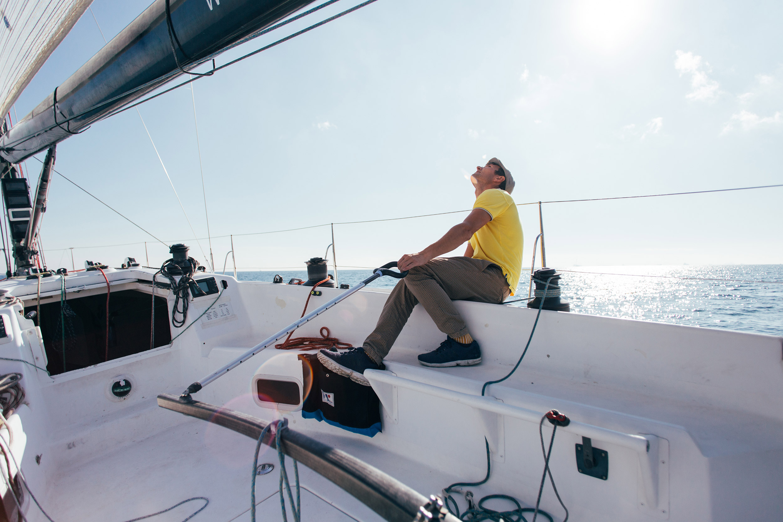 	A man sitting on a sailboat and looking up at the sky