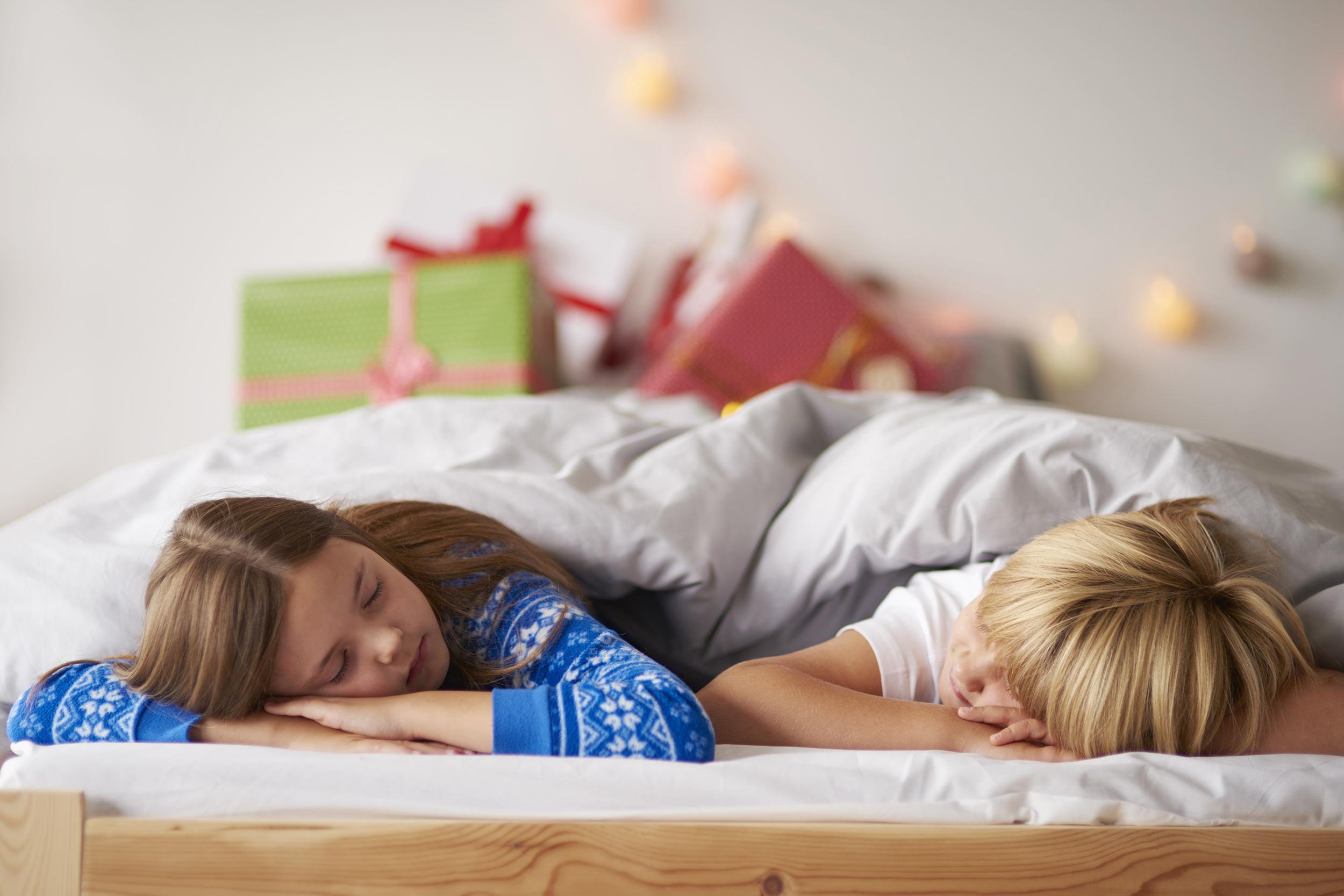 Djevojčica i dječak spavaju u krevetu, djevojčica u plavoj pidžami, dječak u bijeloj majci, pokriveni bijelim poplunom