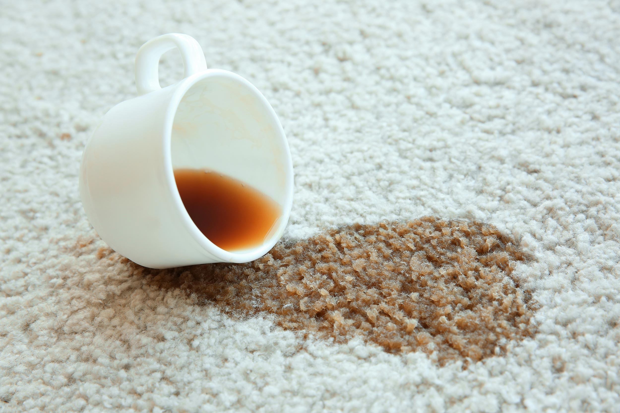 Prolivena kava iz bijele šalice po bijelom tepihu