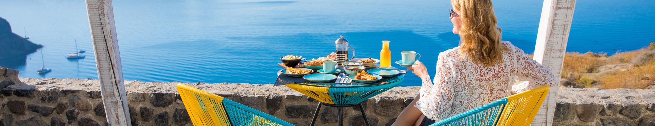 Žena sjedi za stolom na terasi i gleda u more u daljini, u ruci drži šalicu, a na stolu ispred nje pribor za jelo i namirnice za doručak