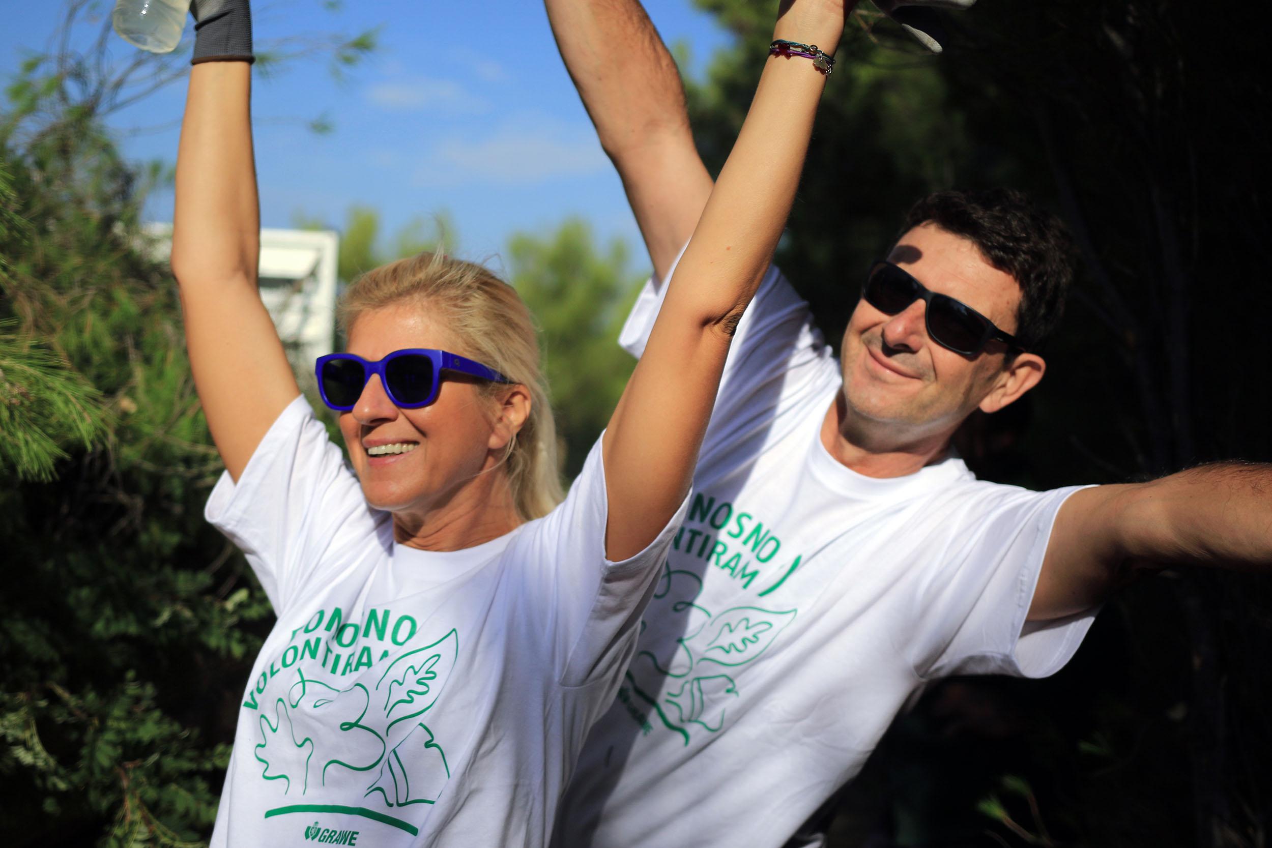GRAWE volonteri, muškarac i žena dignutih ruku u bijelim majicama na kojima piše 'Ponosno volontiramo'