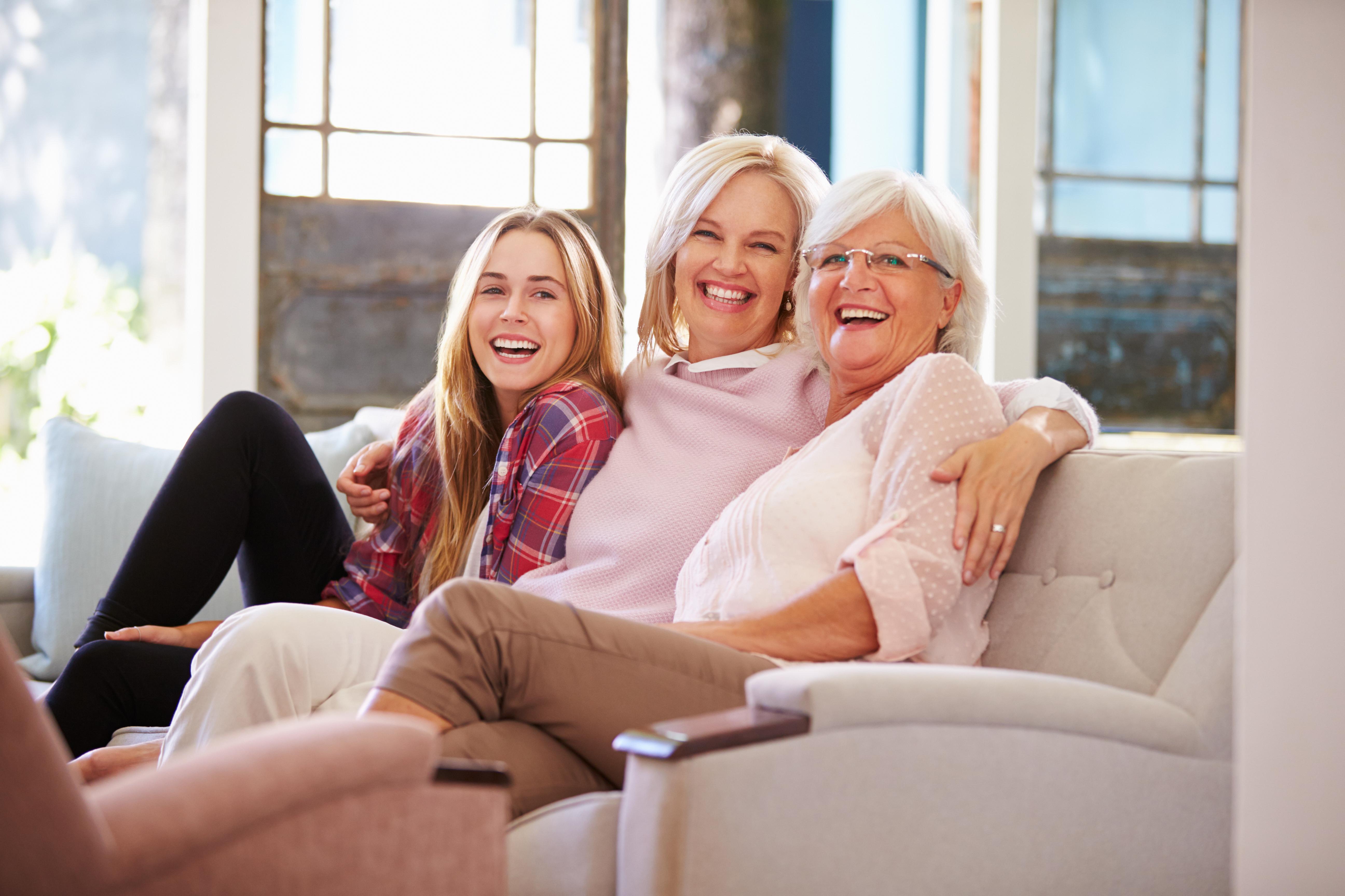Tri generacije: kćer, majka i bak sjede zagrljene na kauču i smiju se