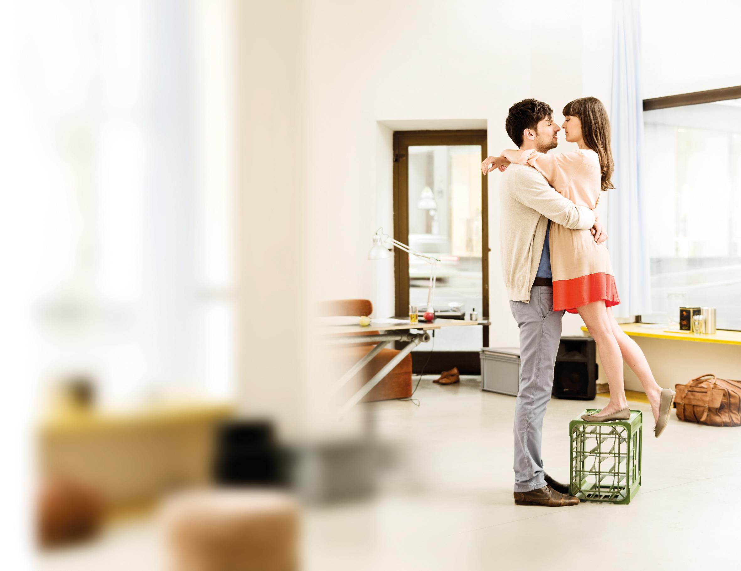Mladi par se grli u dnevnoj sobi