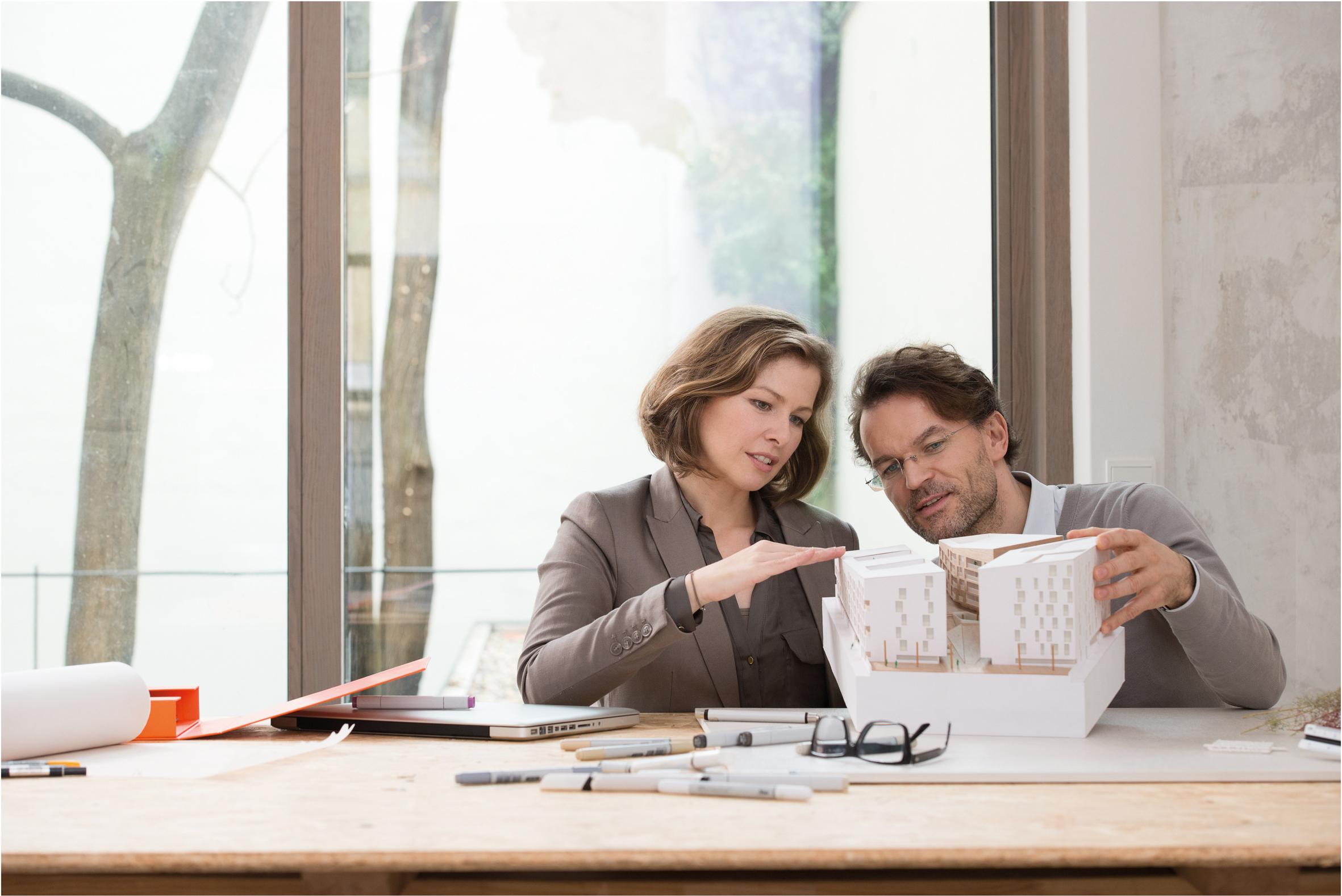Muškarac i žena sjede za stolom na kojem su prijenosno računalo, olovke, naočale i papiri te drže u ruci maketu
