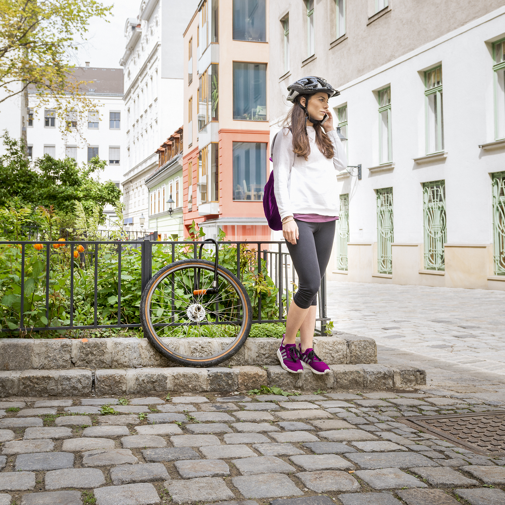 Djevojka s kacigom razgovara na mobitel pored gume od bicikla koji je ukradeen, a ostala je samo guma vezana za ogradu