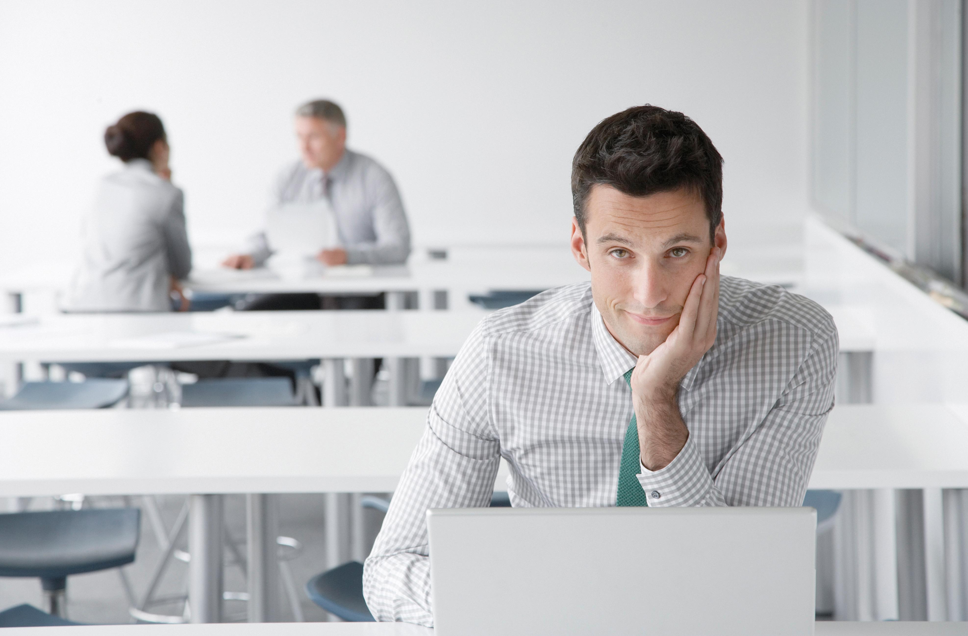U prvom planu muškarac za prijenosnim računalom u uredu u open space prostoriji, u drugom planu muškarac i žena na sastanku