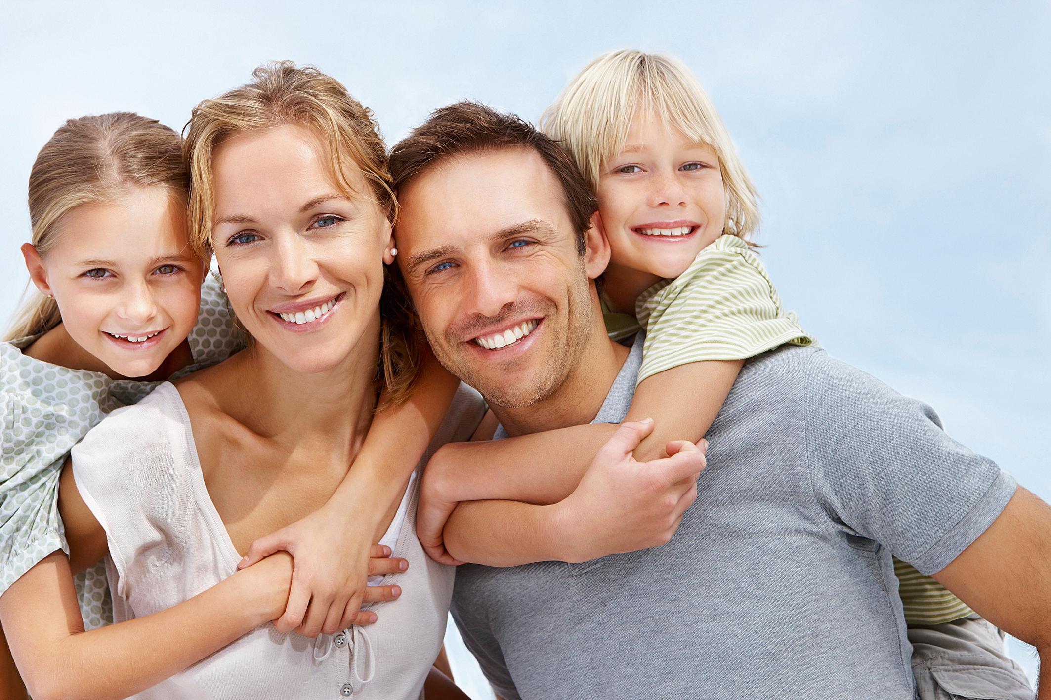Mlada obitelj: kćer grli mamu oko vrata, pored stoji otac kojeg sin grli