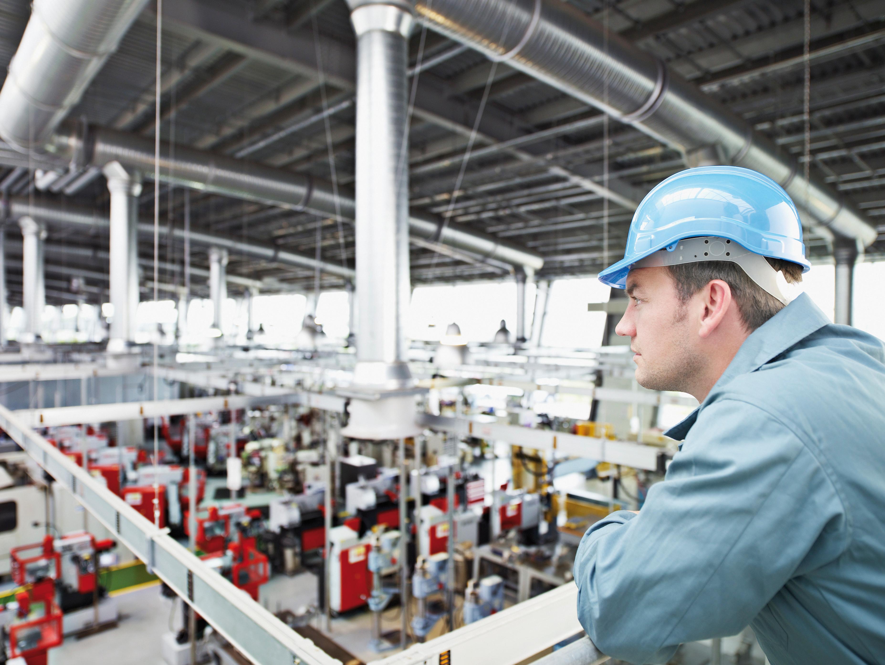 Radnik s kacigom u radnom odijelu u tvorničkom pogonu