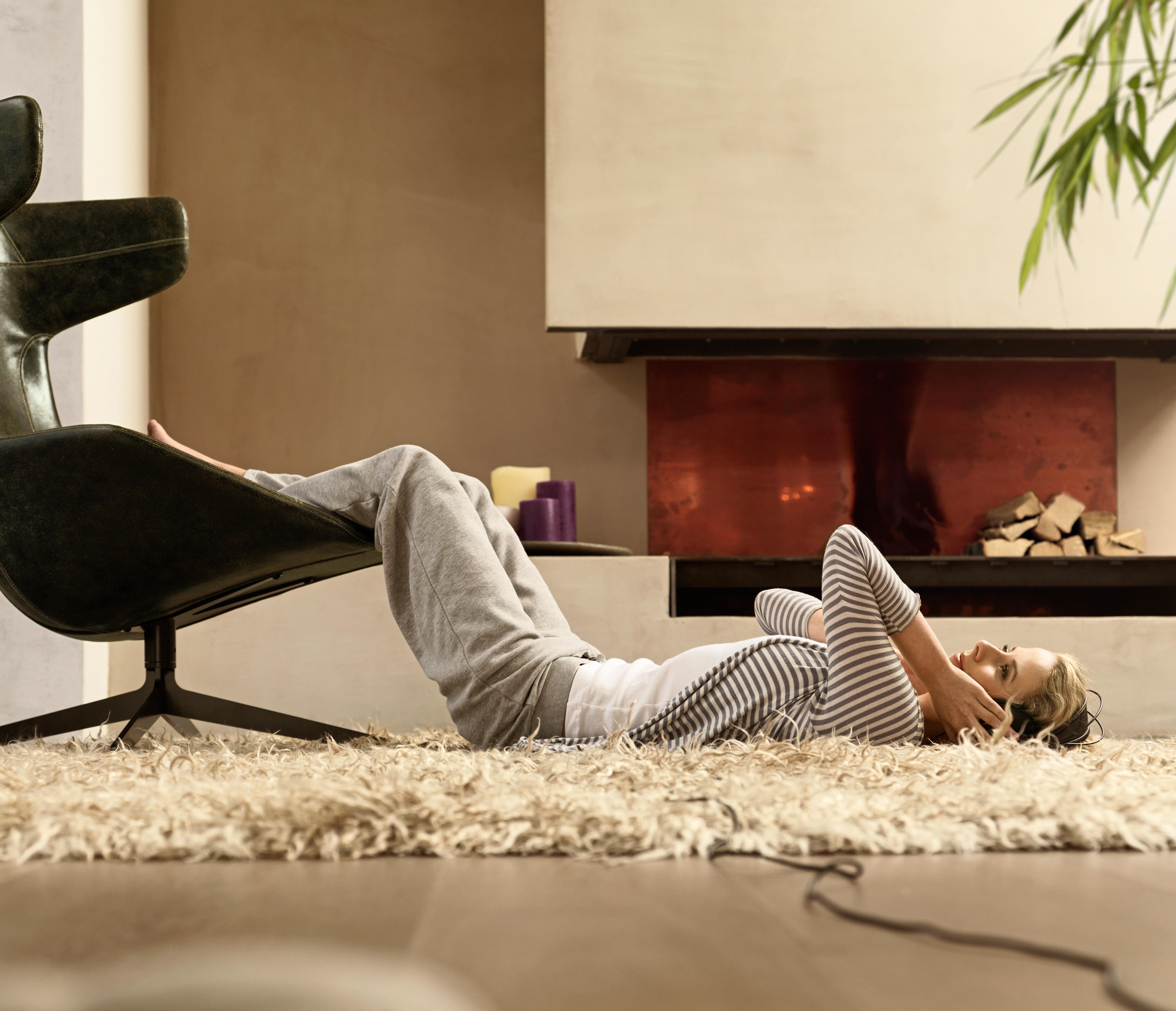 Djevojka leži na tepihu u dnevnoj sobi s nogama podignutima na kožnoj fotelji, u pozadini kamin