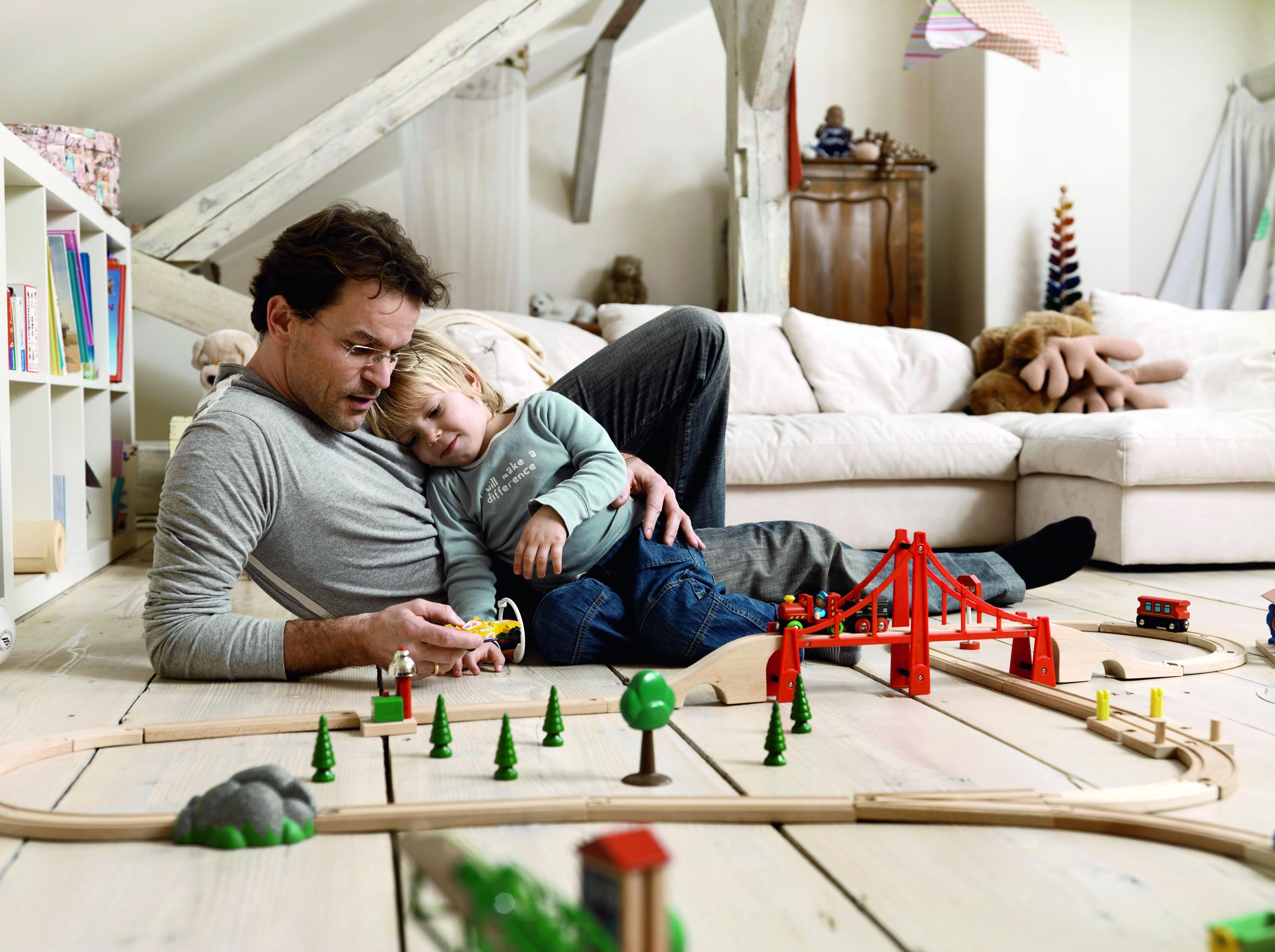 Otac i sin leže na podu dnevne sobe, otac drži mobitel, sin naslonjen na oca spava, ispred njih drvene igračke željeznice