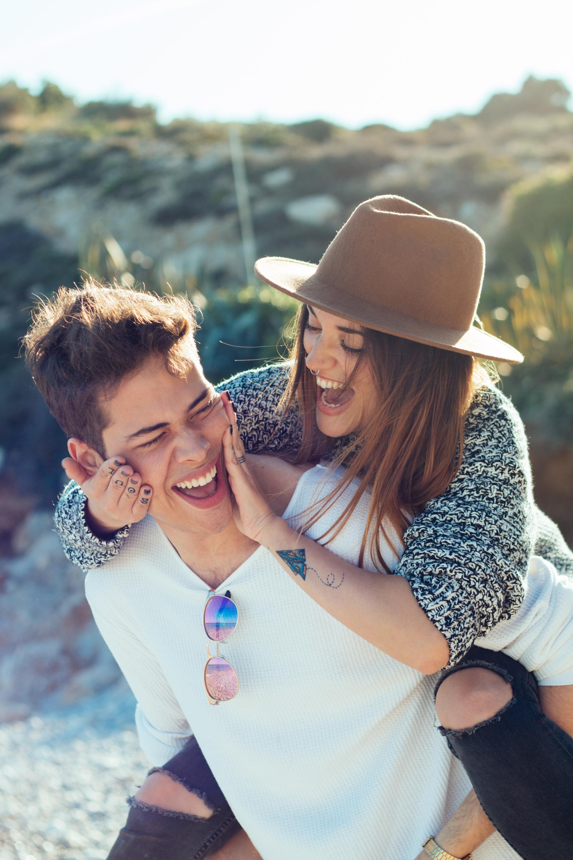 Mladić i djevojka u šeširu, on nju nosi na leđima, smiju se